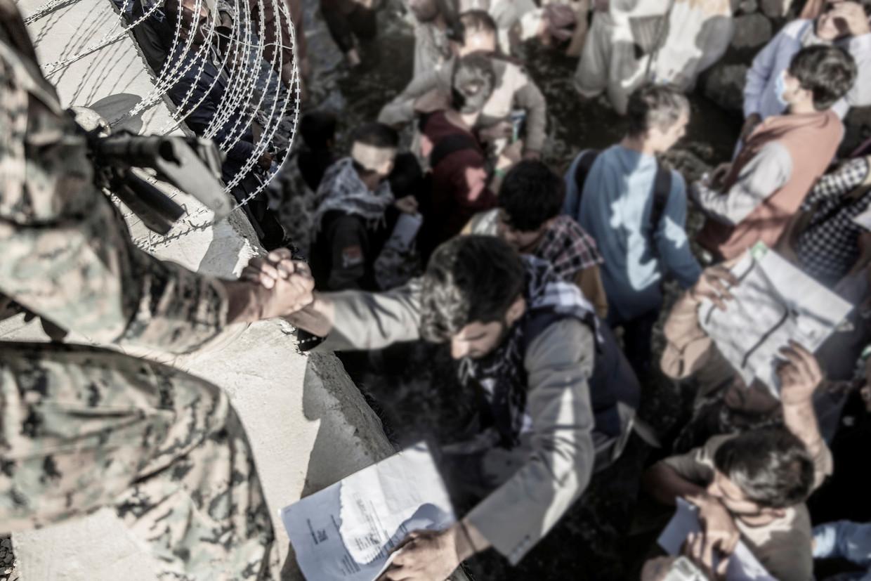 Amerikaanse militairen helpen evacués om toegang te krijgen tot Hamid Karzai International Airport in Kaboel op 26 augustus.