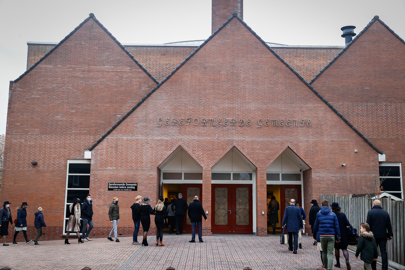 Kerkgangers komen aan bij de Rehobothkerk voor de wekelijkse kerkdienst.