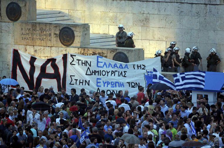 Het Griekse woord voor 'ja' prijkt op talrijke banners tijdens een pro-europese betoging voor het Griekse parlementsgebouw in Athene. Beeld REUTERS