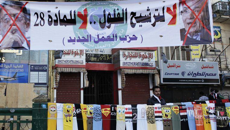 Een t-shirtverkoper onder een spandoek waarop de tekst: 'Nee tegen kandidaten van het oude regime' staat. Rechts een foto van Shafiq, met een kruis erdoor. Beeld ap