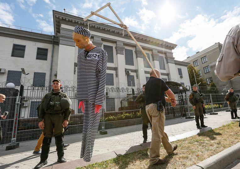 Een betoger loopt met een opgeknoopte Poetin-pop voor de Russische ambassade in Kiev. Beeld EPA