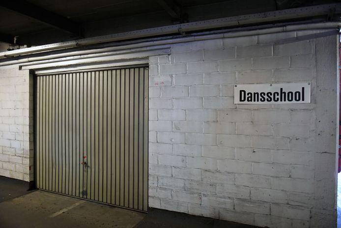 Achter deze garagepoort was een woning. Getuige het 'huisnummer' rechts bovenaan de poort (inzet).
