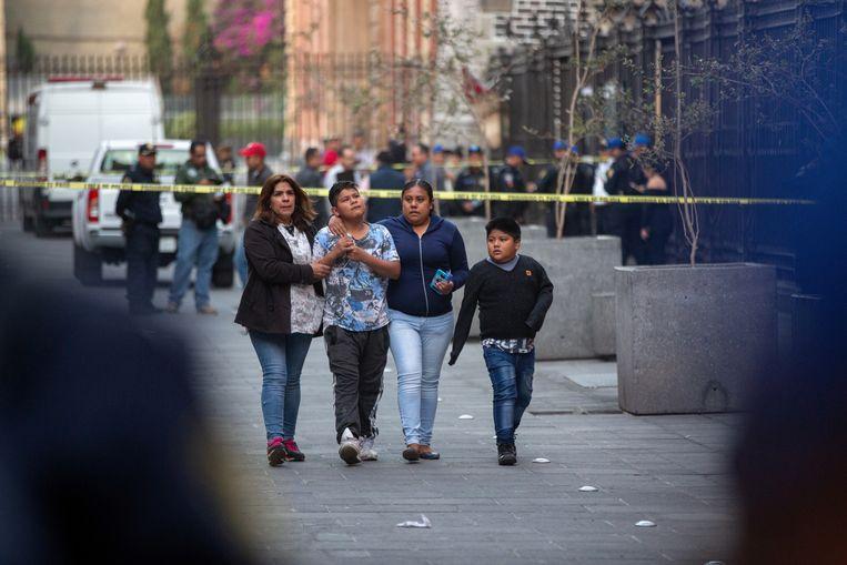 Aangeslagen omstanders op de plek waar ten minste vier doden vielen en twee mensen gewond raakten bij een schietpartij.  Mexico-Stad, 7 december 2019.