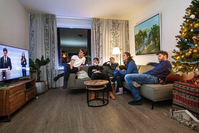 Het gezin De Bree kijkt naar persconferentie Mark Rutte. Alleen zoon Coen ontbreekt, die zit op zijn kamer in quarantaine.  Beeld Guus Dubbelman / de Volkskrant