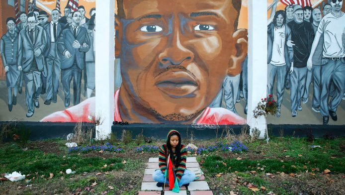 Een meisje zit voor een grote muurschildering van Freddie Gray