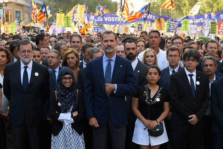 De Spaanse koning Felipe VI tussen toenmalig premier van Spanje Mariano Rajoy en toenmalig Catalaans president Carles Puigdemont (r) in een mars tegen terrorisme met de slogan #NoTincPor (ik ben niet bang) op 26 augustus 2017. Beeld AFP