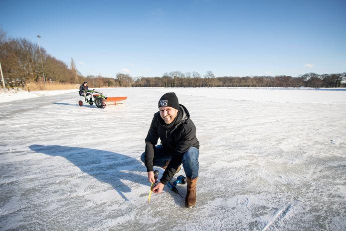 Henk-Jan Vissia, voorzitter van de stichting IJsbaan Almelo, controleert het ijs op dikte. Even later klinkt het sein dat vanaf 16.00 uur in Almelo geschaatst kan worden. Wie het eerst komt, het eerst maalt.