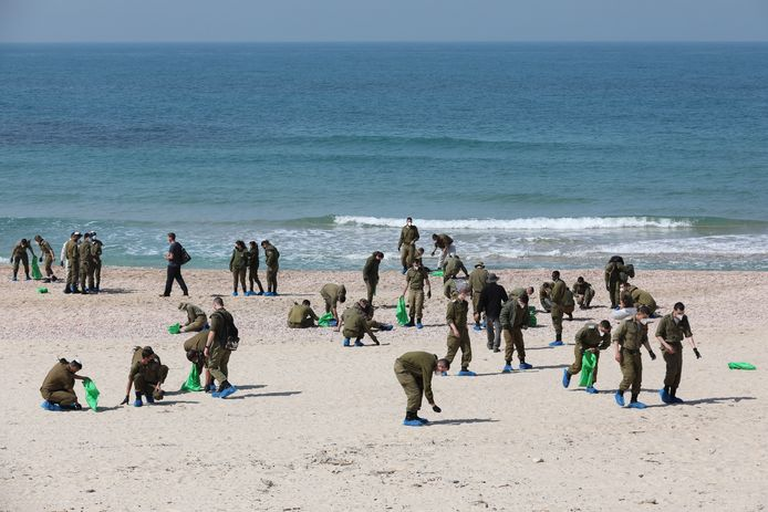Israëlische soldaten in de weer met het opkuisen van de aangespoelde stukken teer op het strand.