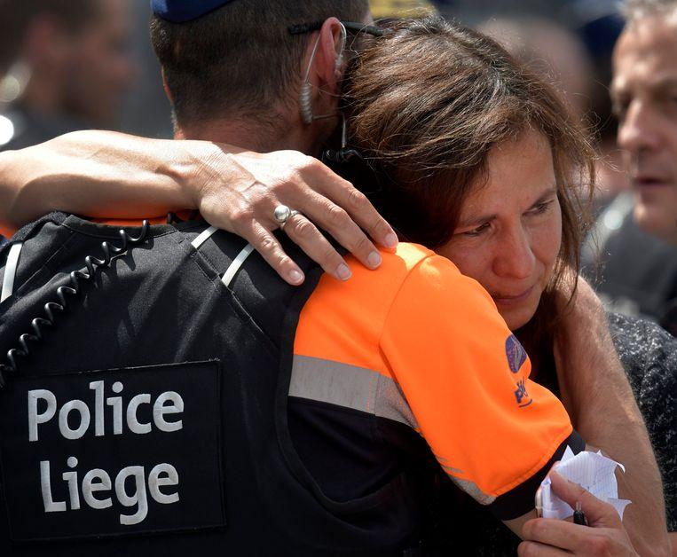 Een vrouw omhelst een Luikse politieagent tijdens de minuut stilte.  Beeld Photo News