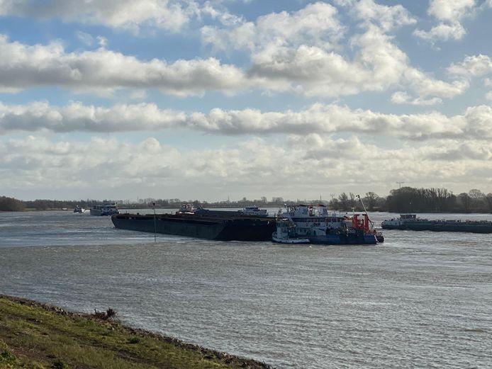 De bij Opijnen gestrande duwbak ligt goed in de weg voor de overige schepen op de drukbevaren Waal.