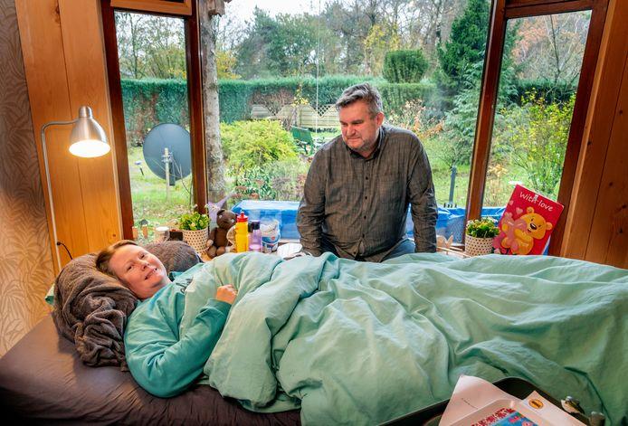 Mariëlle de Vries op bed in haar chalet in Putten. Haar vriend Richard van Os is bij haar.