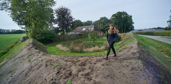 Olga Meulenbroek op de metershoge aarden wal rond haar woning in Zeeland. In het midden haar huis, rechts achter boven de mais is nog net de Heijderhoeve zichtbaar.
