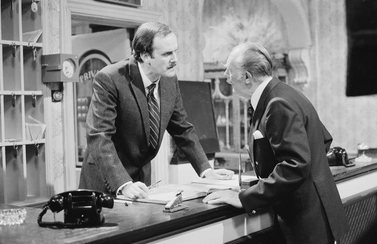 John Cleese (l.) en Ballard Berkeley als Major Gowen. 'We steunden zijn mening niet, we wilden die net belachelijk maken', zegt Cleese over het racistische personage. Beeld Radio Times via Getty Images