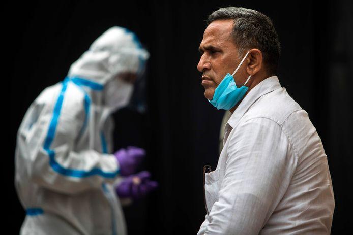 Een man wacht om getest te worden op het coronavirus in New Delhi, India.