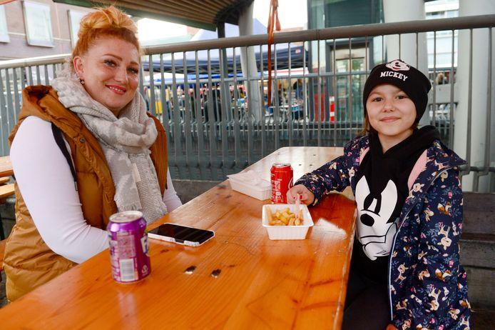 Jana en dochter Lia uit Duitsland genieten deze zaterdag op de Enschedese markt van patatjes, 'Frei von Maske!' Bij de oosterburen zijn de coronamaatregelen veel strenger dan in Nederland.