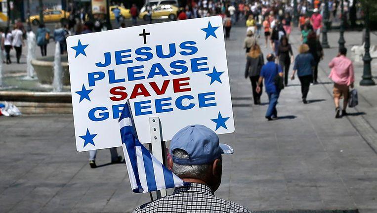 Een Griekse man bidt voor goddelijke hulp op het Syntagmaplein in Athene. Beeld REUTERS