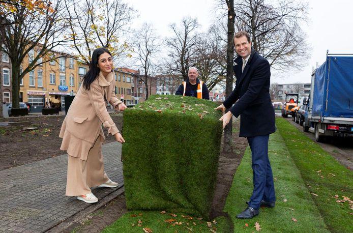 Wethouder Hilbert Bredemeijer en bewoner Ebru Akkus leggen graszode in het hondenveldje aan de Delftselaan