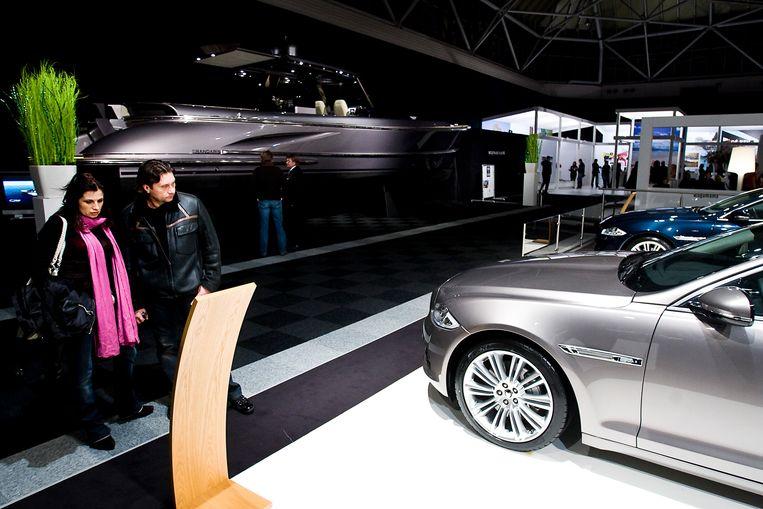 Bezoekers kijken maandag naar een nieuwe Jaguar op de Miljonair Fair in de Amsterdam RAI. Beeld Hollandse Hoogte /  ANP