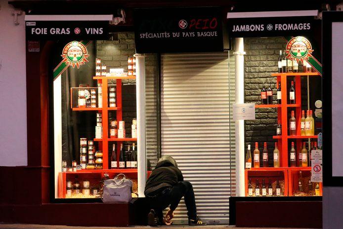 Een winkelier in het zuidwestelijke Saint Jean de Luz sluit iets voor 18.00 uur zijn zaak af.