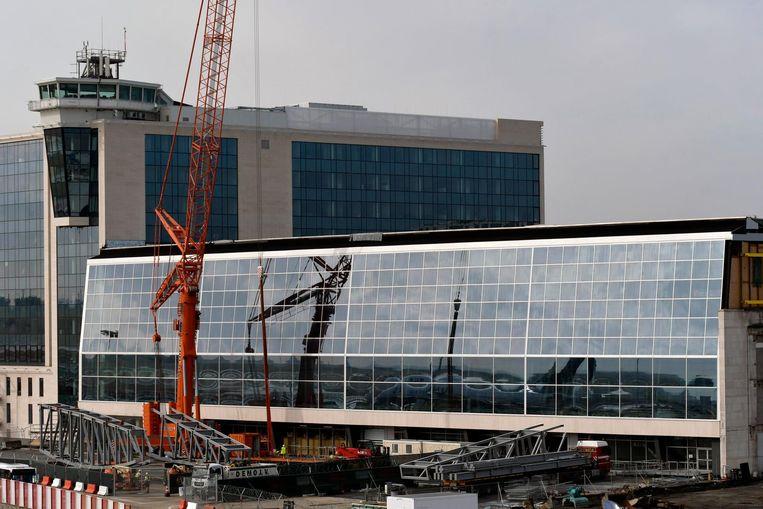 Een stalen kraan van 700 ton begint stalen spanten van 55 meter en 53,5 ton naar boven te hijsen aan de Sky Hall van de luchthaven.