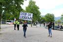 Een vrouw op de Koekamp in Den Haag met een bord waarop valt te lezen: 'Stop de lockdown'.