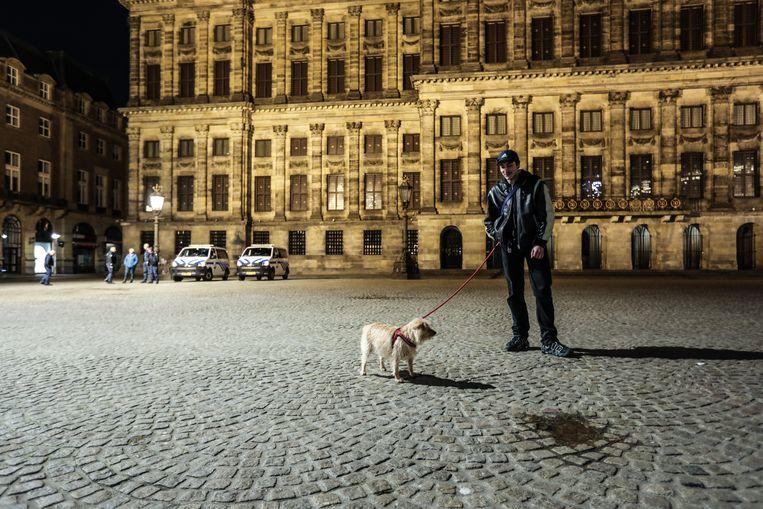 Op de Dam wandelt een man met zijn hond tijdens de avondklok. Naarmate de tijd verstreek, namen steeds meer hondenbezitters bezit van de stad. Beeld Eva Plevier