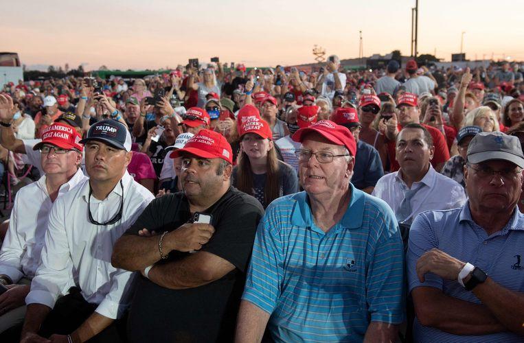 Trumps aanhangers zitten dicht op elkaar zonder 1,5 meter afstand tot elkaar te houden en dragen geen mondkapjes. Beeld AFP
