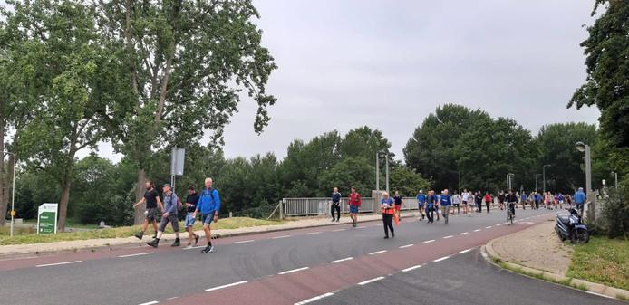 Onder aanmoedigend getoeter van verkeer op de A325 lopen de lopers van de 50 kilometer vanuit Elden in de richting van Huissen.