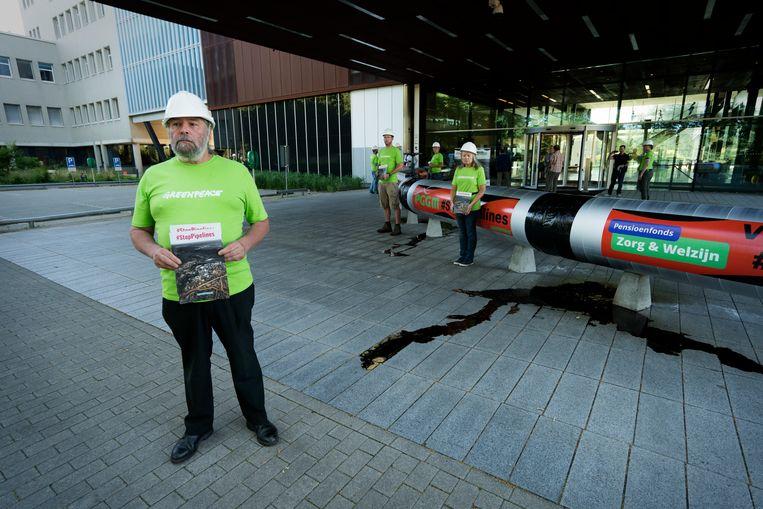 Greenpeace voert actie voor de hoofdingang van PGGM. PGGM is de vermogensbeheerder van Pensioenfonds Zorg en Welzijn (PFZW). Greenpeace wil met deze actie aandacht vragen voor beleggingen van het pensioenfonds in het milieubelastende teerzandolie. Beeld Hollandse Hoogte / Robbert Frank Hagens | Art in Media