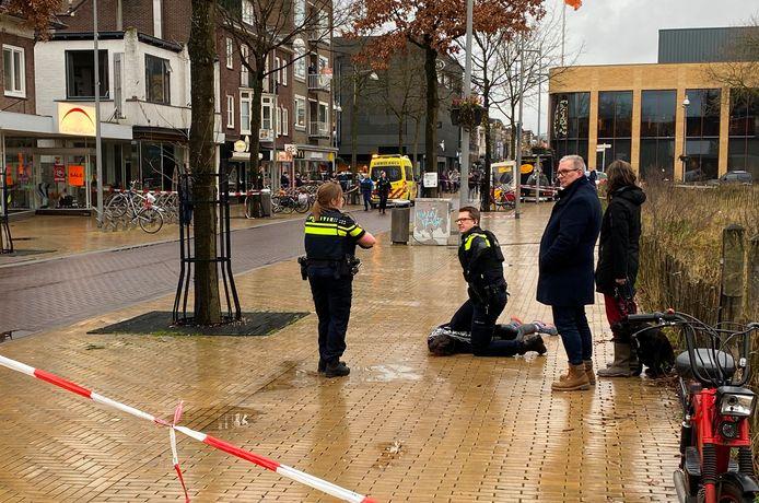 Agenten bewaken een persoon op straat.
