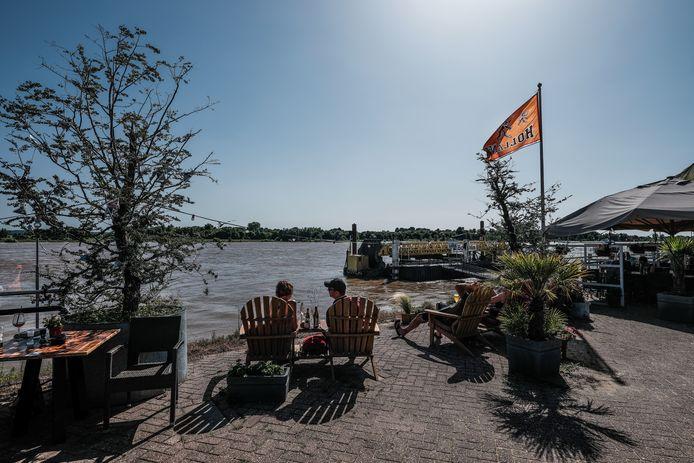 Hoogwatertoeristen bekeken afgelopen weekend  onder het genot van een biertje het stijgende water in de Rijn bij Tolkamer.