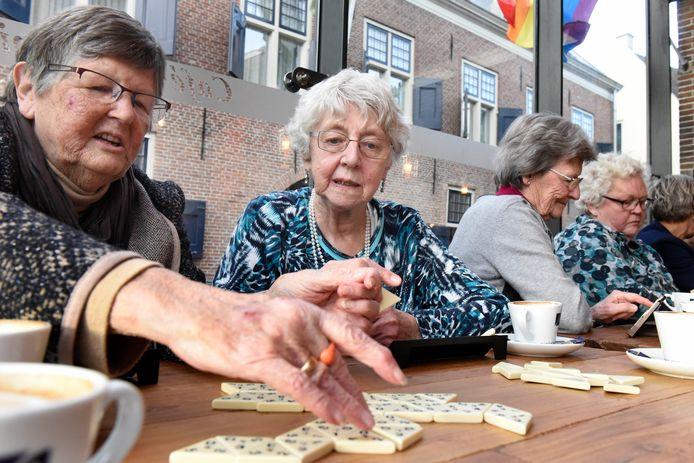 Oudere alleenstaanden spelen een spelletje in het Thuishuis Café in de Pompier