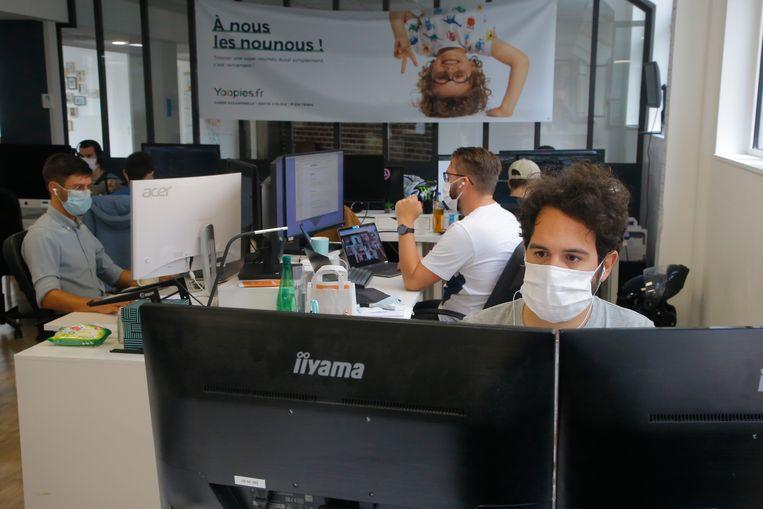 Ook op kantoor houden de werknemers zich aan de mondkapjesplicht. Beeld AP
