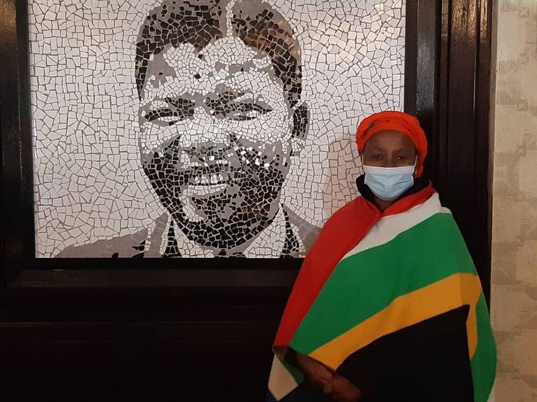 De hoteleigenaar, gekleed in de kleuren van de Zuid-Afrikaanse vlag. Beeld Mark Schenkel