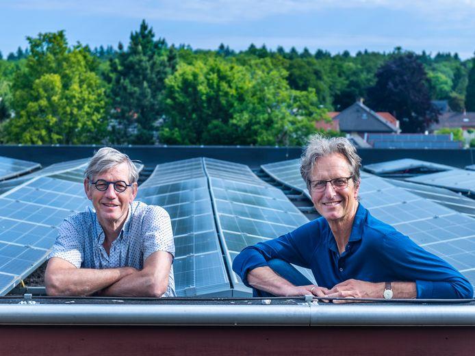 Bestuursleden van Heuvelrug Coöperatie Energie Huis de Vriend en Martijn de Loor op het dak van een sporthal met zonnepanelen. Zo zien ze het graag. Windmolens moeten er ook komen, want alleen stroom van zon is niet voldoende.
