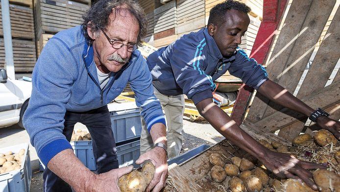 Wim Bosland (l) en Hassan Shidane Baraale laden de aardappels in voor de voedselbank