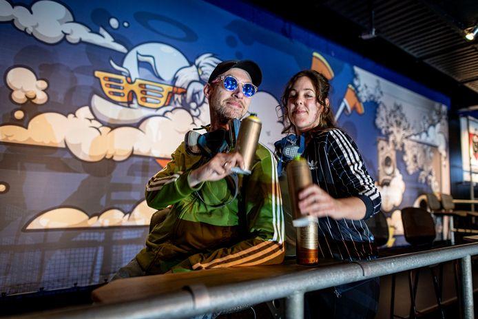 Op het balkon van de Jupiler Stage van Metropool 'proosten' Don Slizerone en Nina Paintina met hun spuitbussen op een geslaagde klus. Ze hebben hier aan een luchtthema gewerkt.