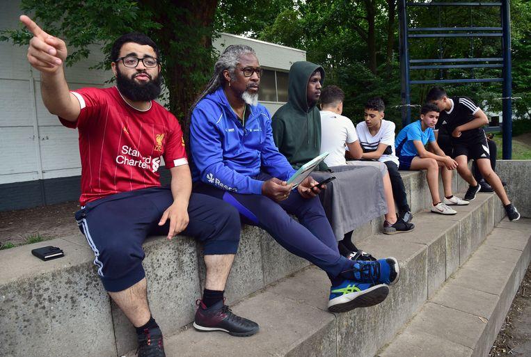 Aan de kant bij het Cruyff Court zitten vrijwilliger Younes Aknin, buurtsportwerker Dennis Drenthe en hardlooptalent Ilyas Osman  Beeld Marcel van den Bergh / de Volkskrant