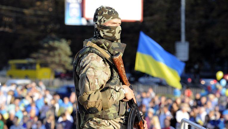 Een Oekraïense soldaat houdt de wacht bij een pro-regeringsbijeenkomst in de zuidelijke havenstad Marioepol. Beeld afp