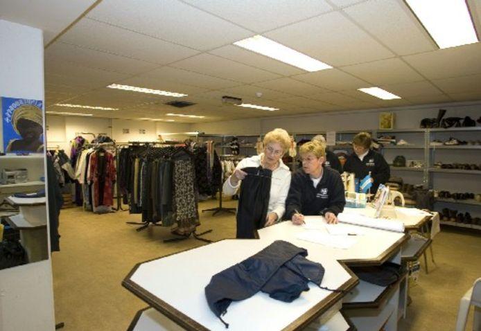 In de SOS-kledingwinkel in Putten toont Marga Streefkerk een van de vele kledingstukken, die voor een heel schappelijk prijsje de winkel uitgaan. De zaak in de kelder van Stroud is flink opgeknapt. Foto TOM VAN DIJKE