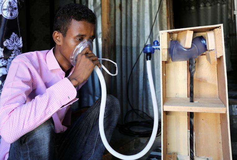 De 21-jarige Mohamed Adawe, een mechanische ingenieur, test zijn zelfgemaakte beademingsapparaat in de Somalische hoofdstad Mogadishu. Beeld REUTERS