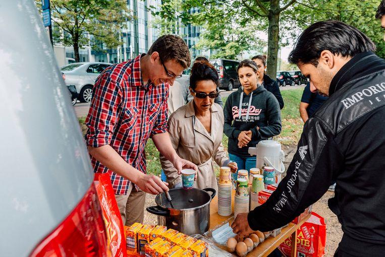 Burgers delen voedsel uit voor de Dienst Vreemdelingenzaken. Beeld Illias Teirlinck