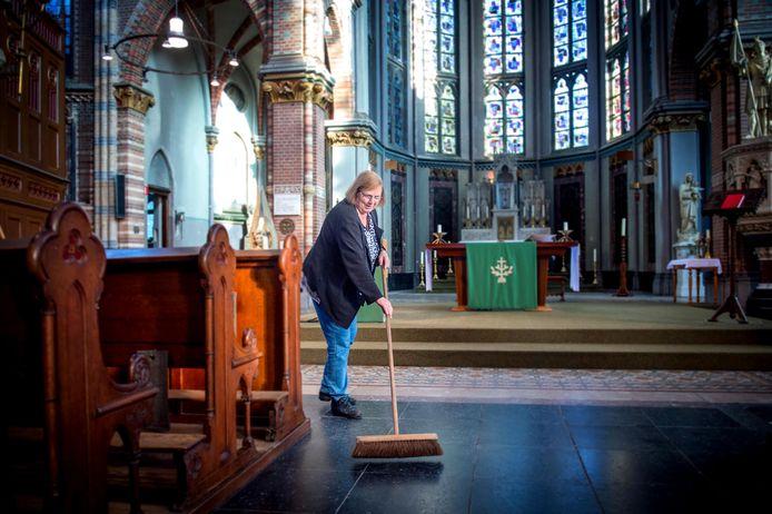 Dorien Geurts veegt de kerk voor de afscheidsmis.