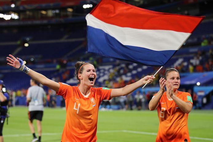 Merel van Dongen zwaait met de vlag na de zege op Zweden. Rechts Sherida Spitse.