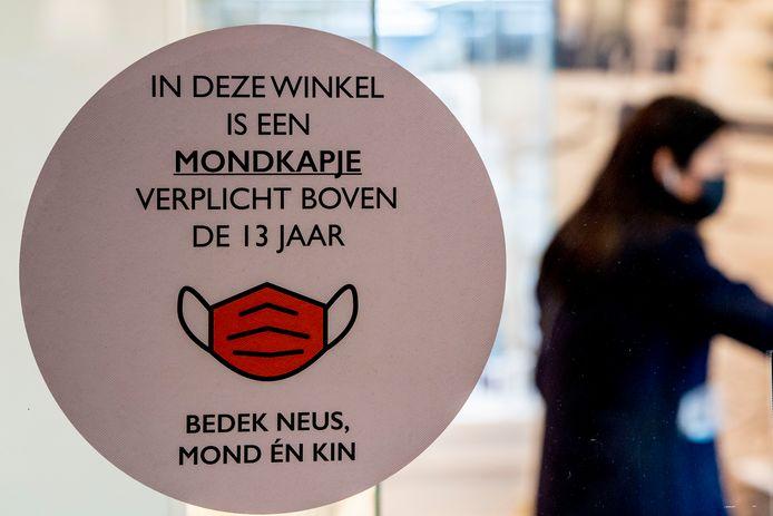Stickers bij de entree van winkels informeren publiek over de mondkapjesplicht.