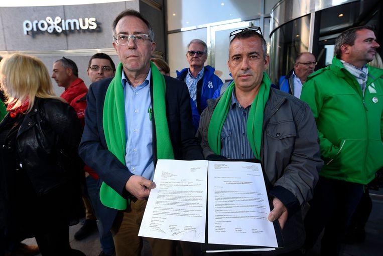 ACV'er Ben Coremans (links) bij de overhandiging van een open brief waarin de vakbonden het onmiddellijke ontslag vragen van Proximus-CEO Dominique Leroy. Beeld Photo News