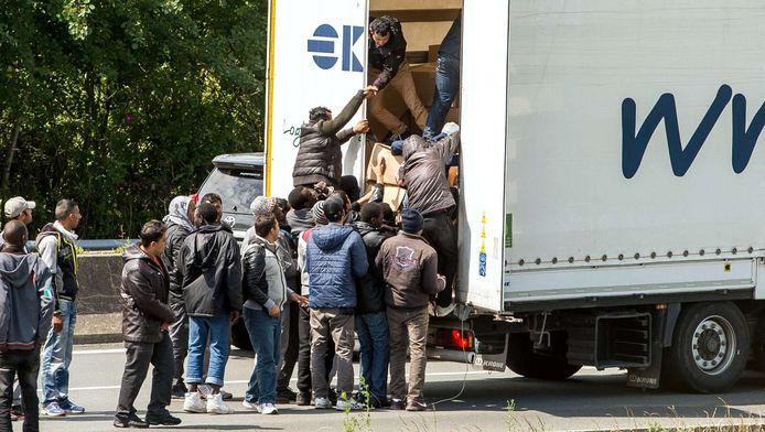 Migranten maken van de gelegenheid gebruik en bestormen de stilstaande trucks.