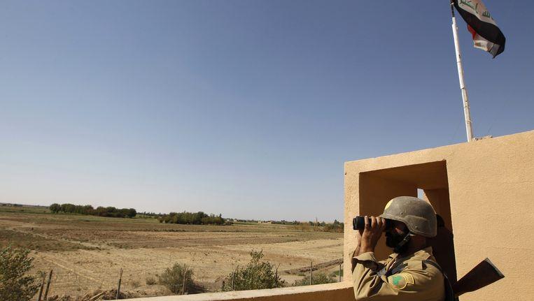 Een Irakese grenspolitieagent op een grenspost op de grens tussen Irak en Syrie, bij Abu Kamal. (archiefbeeld) Beeld reuters