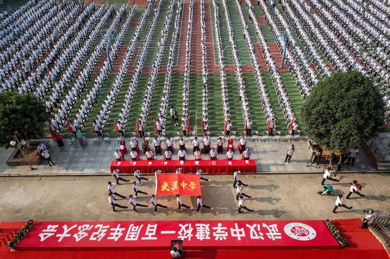 Leerlingen bij de openingsceremonie van het nieuwe schooljaar in Wuhan. Beeld AFP