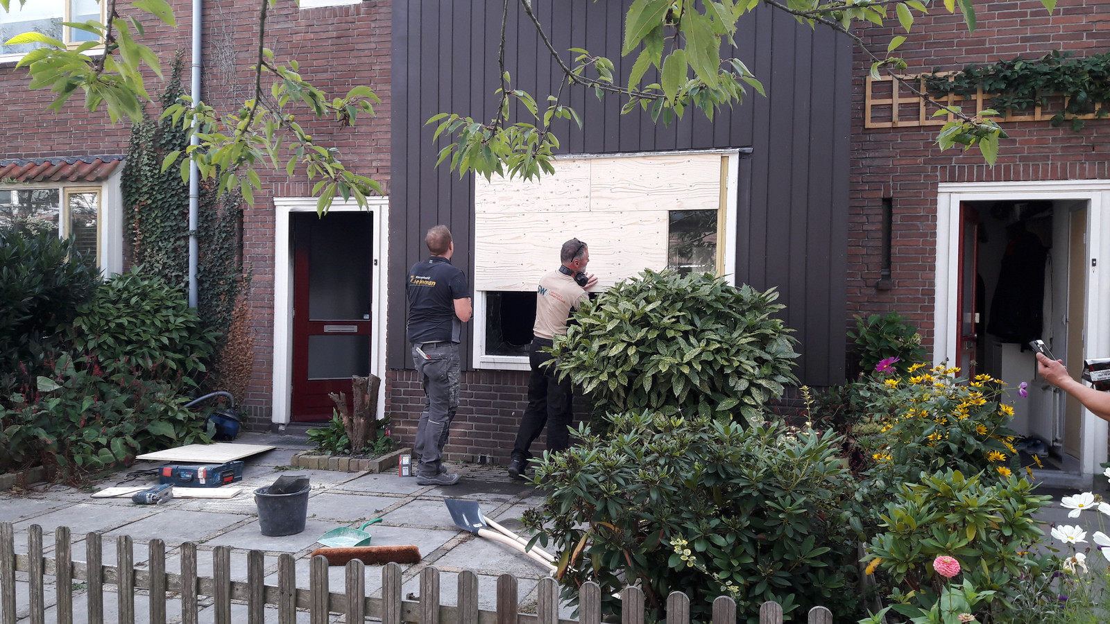 Het kapotte raam wordt dichtgetimmerd bij het huis aan de Seringenstraat in Zwolle.